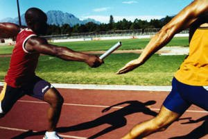 The image shows a relay race where the baton is being handed off.