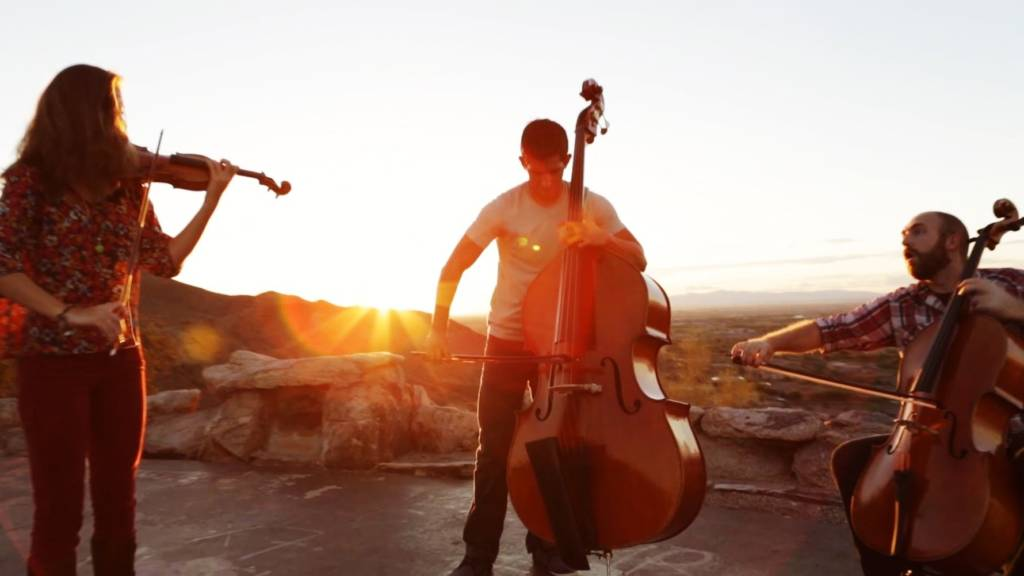 three musicians playing on a rooftop