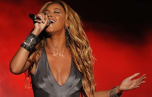 Beyonce singing on stage in red light