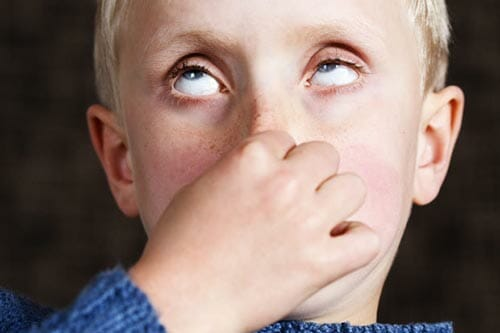 Little blonde boy holding breath by plugging his nose