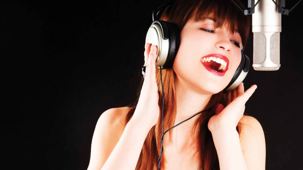 woman singing in front of mic with headphones