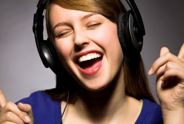 woman with headphones singing and dancing