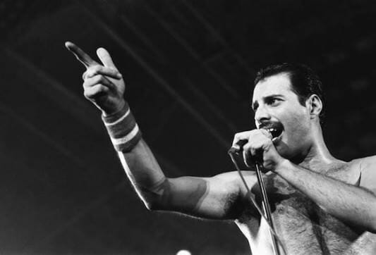 Freddie Mercury singing a high note on stage