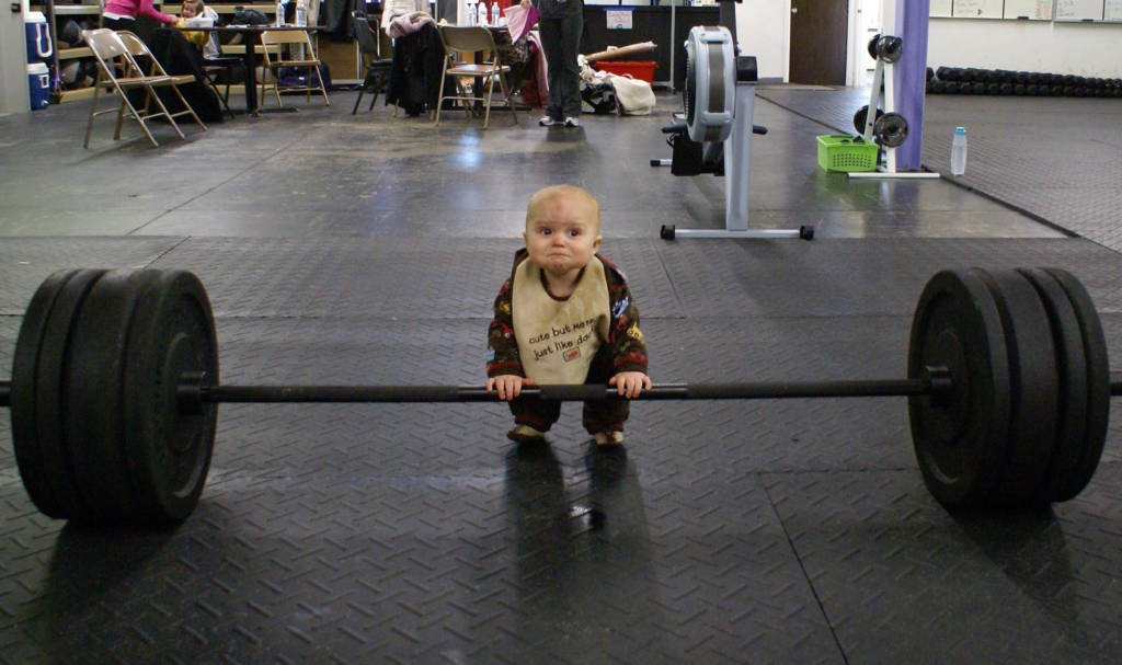 baby in a weight room standing in front of a barbell