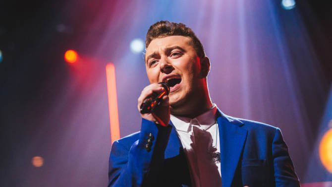 Sam Smith singing with a microphone in his hand