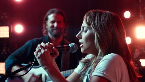 Lady Gaga singing at a microphone while Bradley Cooper plays guitar in the background.