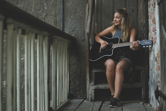 A young blonde woman playing an acoustic guitar sitting on wooden steps