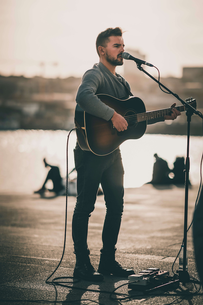 A young man playing acoustic guitar on the boardwalk