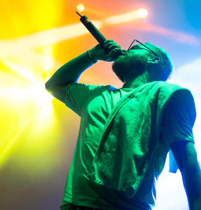 A young man in green light singing into a microphone at an angle