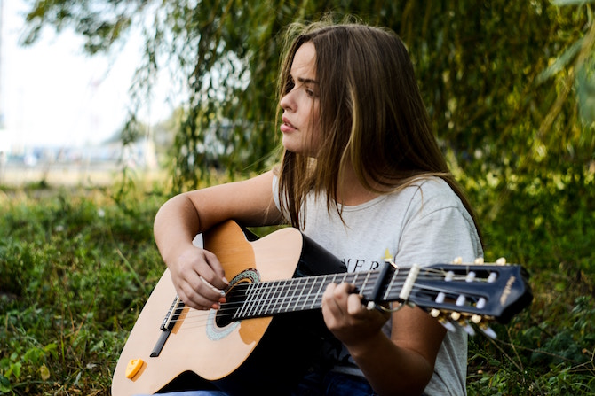 a woman sitting on the grass with a guitar in front of trees