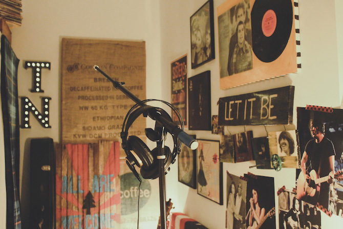 headphones hanging on a mic stand with music posters on the walls