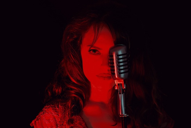 Woman in red light in front of old microphone