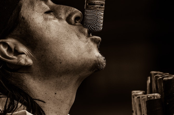 Sepia toned image of a singer close up on a microphone