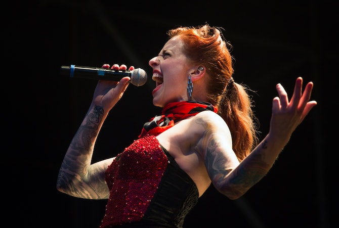 Woman in red with arm tattoos singing intro microphone